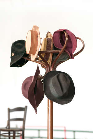A variety of vintage colorful hats hanging on the wooden brown coat rack