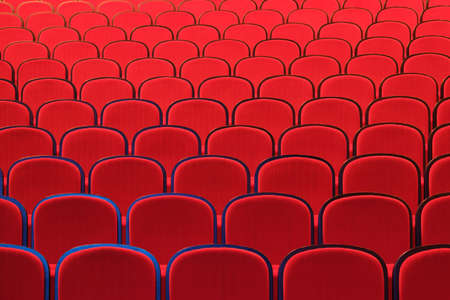 Rows of empty red chairs in concert hall