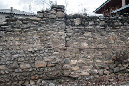 Stone wall with inserts of large stone and bricks
