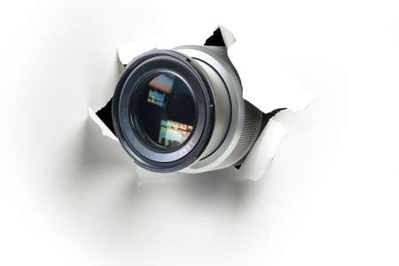 Concept of paparazzi or hidden camera, camera lens looks out through a hole in white paper wall 版權商用圖片