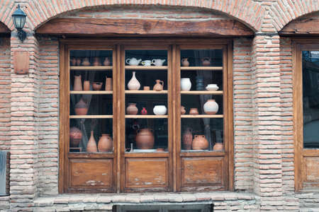 Exterior of an old brick house with wooden showcases with decorative clay ceramic pots and jugs