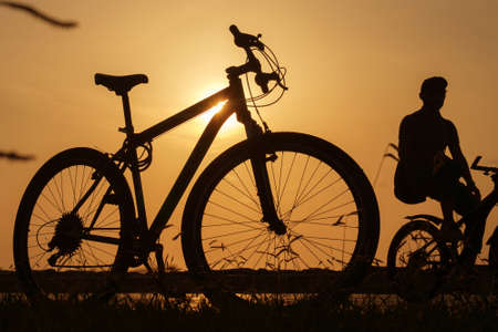 A silhouette of a bike at sunset. The sun shines through the bicycle frame, selective focus 版權商用圖片