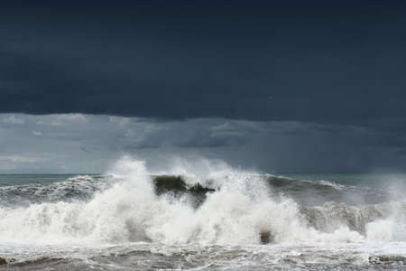 View of a stormy sea and dark cloudy dramatic sky, big waves are crashing on the shore