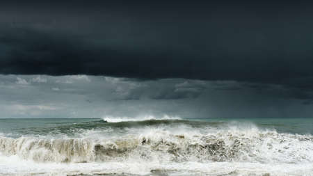 View of a stormy sea and dark cloudy sky, big waves are crashing on the shore