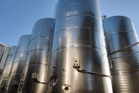 Stainless tanks for processing and fermentation wine production in the open air with blue sky background. Modern wine factory