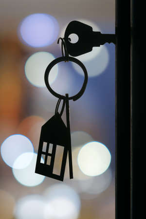 The key with keyring in the door keyhole with blurred night lights background, selective focus Standard-Bild
