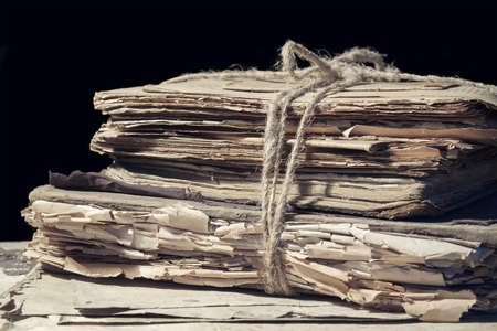 Stack of old papers and books tied with rope Standard-Bild