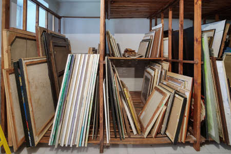 Wooden shelves full of pictures, frames and art equipment. Art gallery storage Standard-Bild