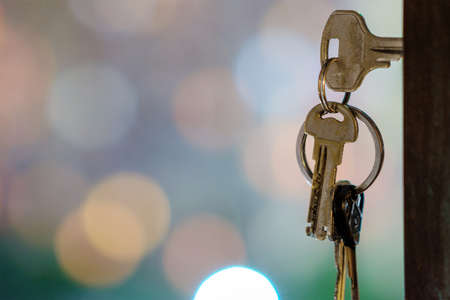 The keys with keyring in the door keyhole with blurred night lights background, selective focus