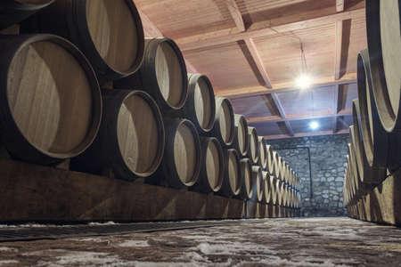 Row of oak barrels in a dry cool wine cellar in basement Standard-Bild