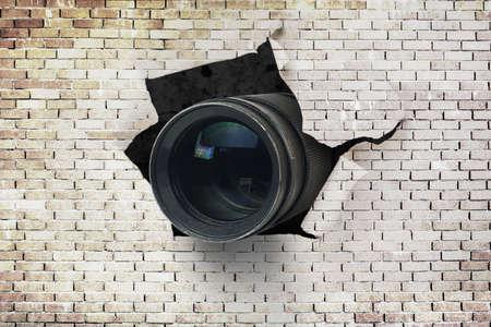 Concept of paparazzi or hidden camera, camera lens looks out through a hole in broken brick wall Standard-Bild