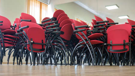 Red chairs stacked in a interior of a large room Standard-Bild