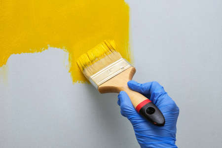 Hand painting the white wall with brush in yellow color