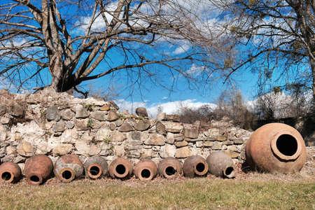 Qvevri, Georgian traditional jug for wine making near the ancient stone wall Standard-Bild