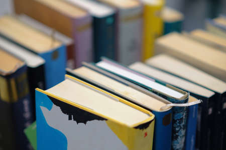A stack of used books of different thicknesses on the shelf in the library, selective focus Standard-Bild