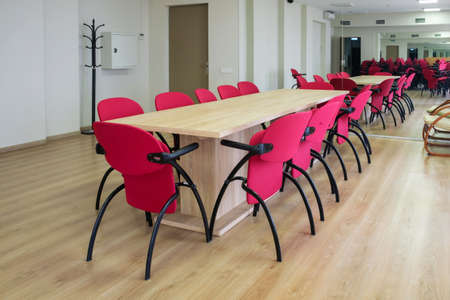 Interior of conference room with large mirrors, big table with red chairs around