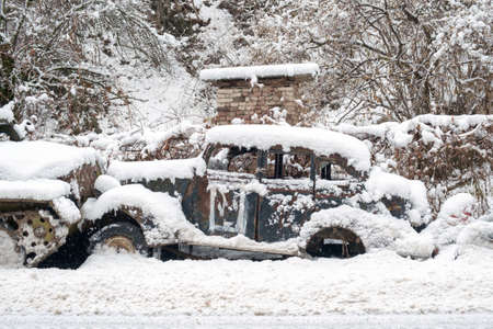 An old vintage broken rustic retro car abandoned in a street covered with snow