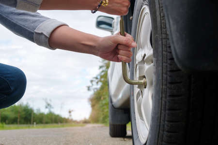 Changing wheel, woman hands unscrewing bolts on flat car tire on the road.