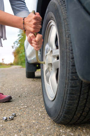 woman changing wheel, hands unscrewing bolts on flat car tire on the road.