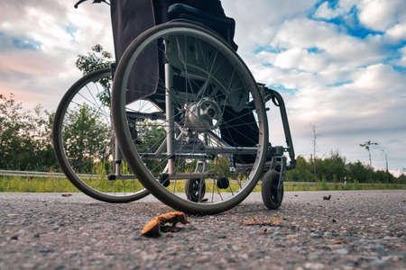 Wheelchair crossing road with overgrown roadsides Standard-Bild