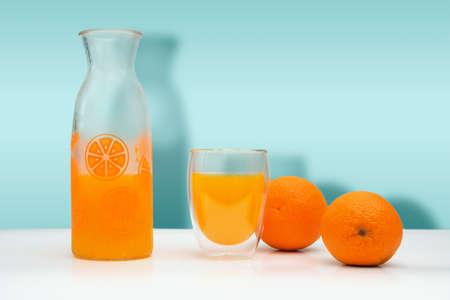 Ripe oranges, a glass bottle and mug with f fresh squeezed orange juice on white background. Standard-Bild