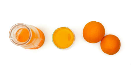 Top view of a ripe oranges, glass bottle and mug with fresh squeezed orange juice on white background. Standard-Bild
