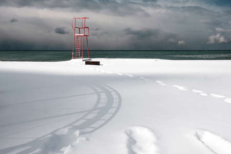 Red lifeguard tower construction on the beach covered with snow Standard-Bild