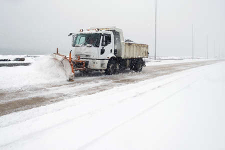 Truck cleaning  winter road covered with snow at the sea side park