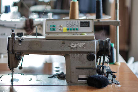 Used sewing machine and sewing tools in fashion atelier, selective focus