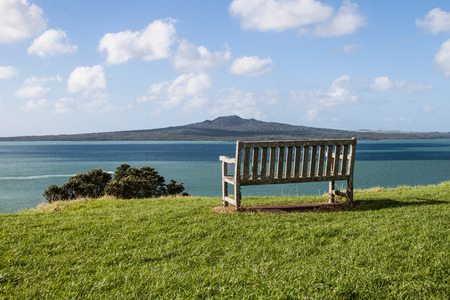 Green landscape with a bench and a volcanic island