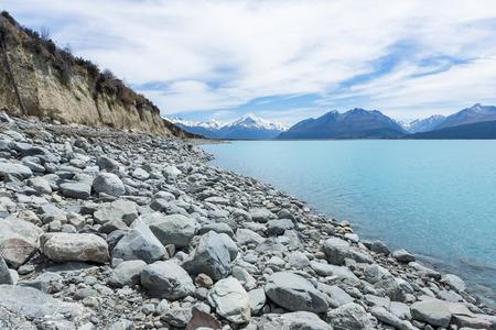Rocky lake shore with snowcapped mountains on a horizon 版權商用圖片