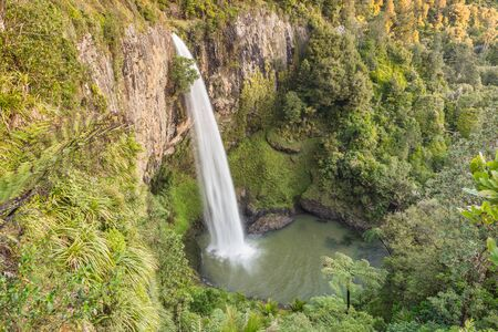 High waterfall falling from a volcanic mountain range to a valley