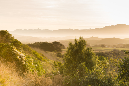 Misty sunset landscape of ranges in the distance