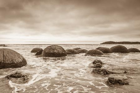 Sepia toned Moeraki boulders stormy landscape 版權商用圖片