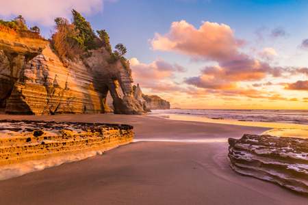 Sunset view of a rocky coast. Tongaporutu beach in Taranaki district, New Zealand, around the famous Three Sisters rock formation Stockfoto