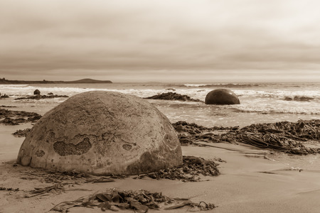 Sepia toned landscape with the famous Moeraki boulders on a beach