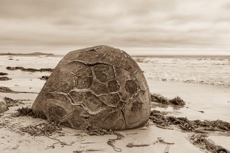 Sepia toned one of the unique Moeraki boulders on a beach in Otago, New Zealand