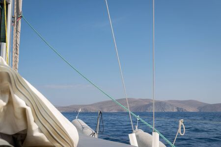 Beautiful view from the deck of a sailing boat. The boat is approaching a small island.