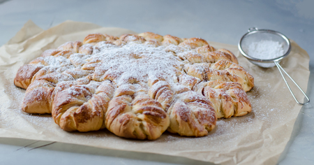 Fresh pastry. Sprinkled with powdered sugar. The shape of a star.
