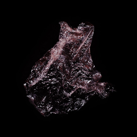Transparent shiny plastic bag on black background. Abstract background.