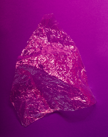 Transparent shiny plastic bag on purple background. Abstract background.