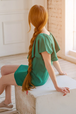 A girl with very long red hair in a green dress. Light from the window Stock Photo