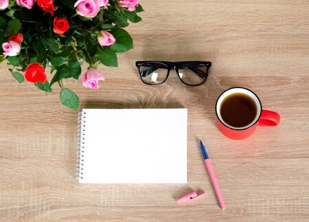 Wooden Desk. White tablet with black-rimmed glasses. Cup of tea. White notebook with space for writing.