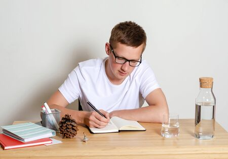 A young man in a white t-shirt sitting at his Desk, writing something in a notebook.
