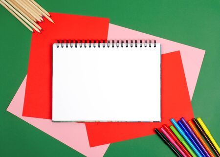 White drawing pad. On the table is colored paper, colored pencils. Bright picture. Possibility to insert your design on a white background.