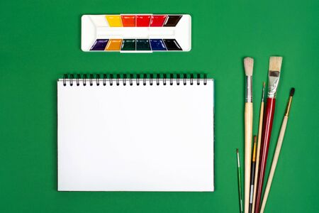 White notebook with paints and brushes for drawing. The photograph on the subject of creativity. Painting. Stock Photo