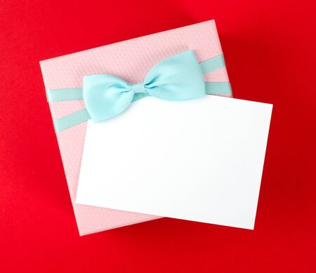 Gift box with bow and white greeting card.