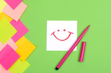 A writing sheet and a felt-tip pen. Green background. Bright stickers on the side. White sheet of paper