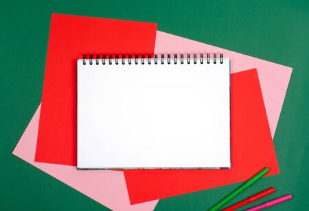 White drawing pad. On the table is colored paper, colored pencils. Bright picture.