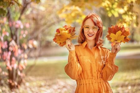 A bright girl with copper-colored hair. Beautiful autumn nature.